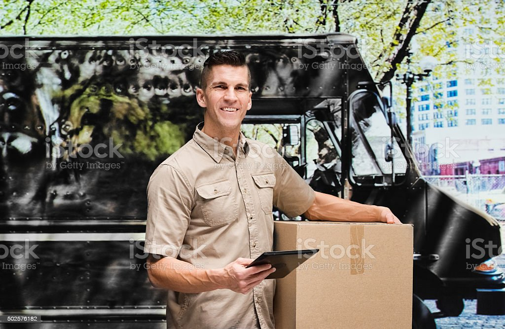 Smiling worker holding tablet outdoors stock photo