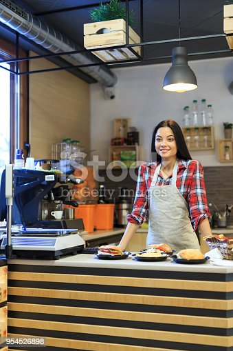 Portrait of smiling fast food worker, standing arms crossed and looking at camera.