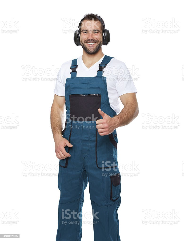 Smiling worker in green uniform with protective earphones royalty-free stock photo