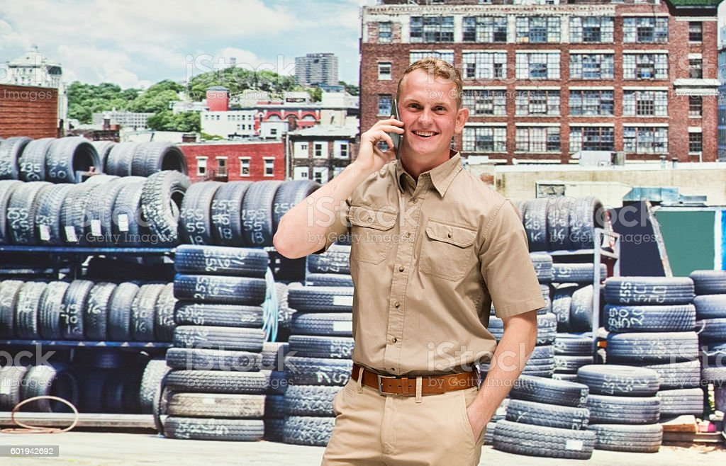 Smiling worker on phone in front of tire factory stock photo