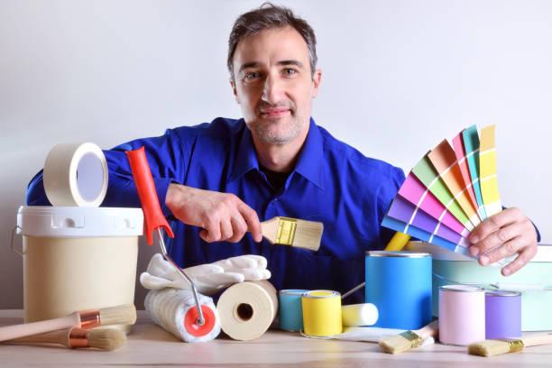 Sonriente trabajador presentando productos y herramientas de pintura sobre tabla - foto de stock