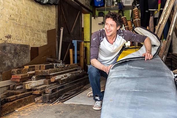 smiling worker removing surfboard from cover in workshop - surf garage bildbanksfoton och bilder