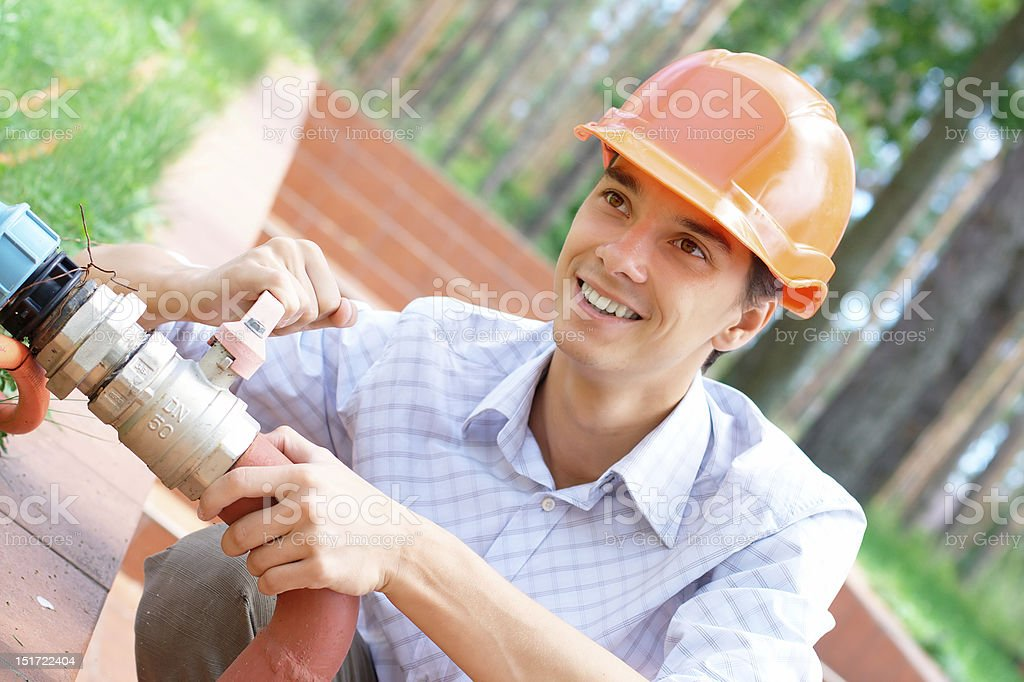 Smiling worker repairing a pipe royalty-free stock photo