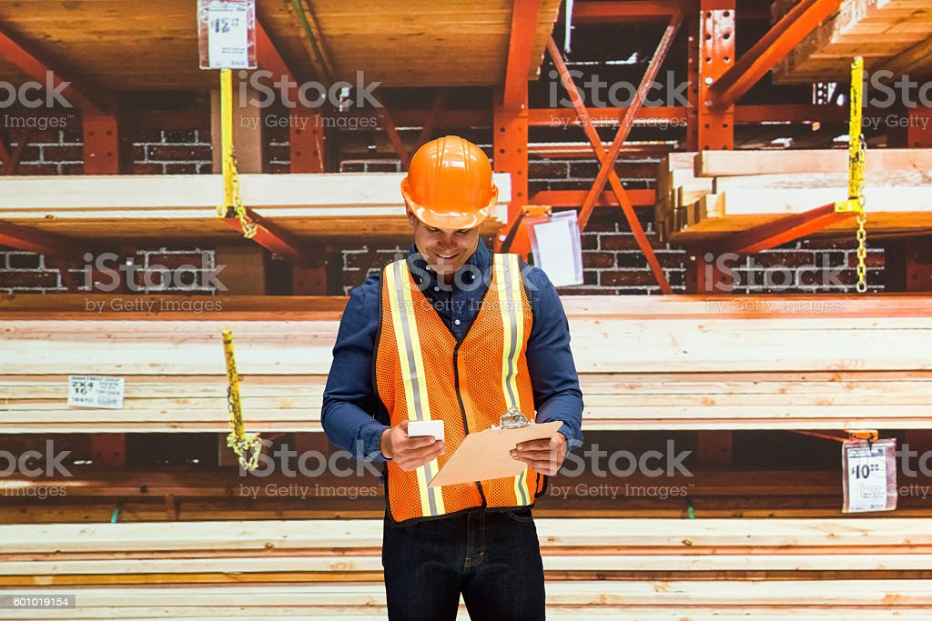 Smiling worker using phone in warehouse stock photo