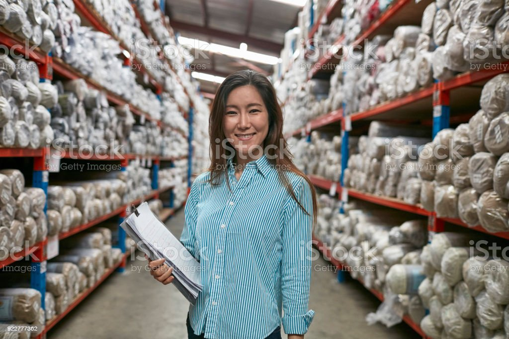 Smiling worker with checklist in carpet factory stock photo