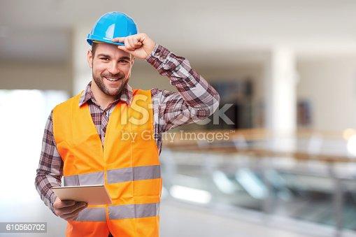 Manual worker in blue helmet with digital tablet