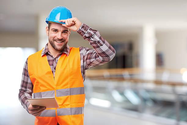 uśmiechnięty pracownik z cyfrowym tabletem - kask ochronny odzież ochronna zdjęcia i obrazy z banku zdjęć