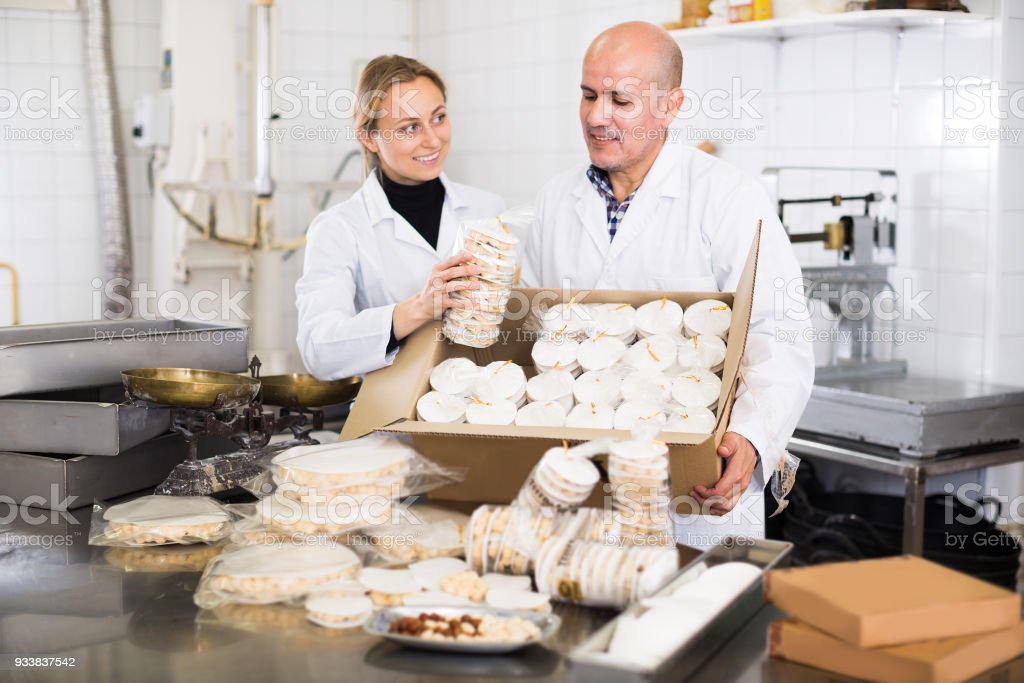Smiling workers standing with box of turron stock photo