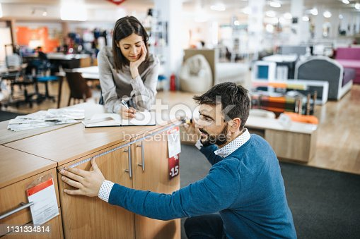 Young couple buying at furniture store. Focus is on man measuring cabinet with tape measure while woman is writing notes.