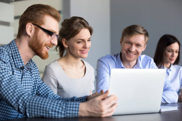 smiling workers watching interesting video at laptop in office - webinar stock photos and pictures