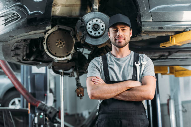 smiling workman posing with crossed arms in auto mechanic shop smiling workman posing with crossed arms in auto mechanic shop auto mechanic stock pictures, royalty-free photos & images