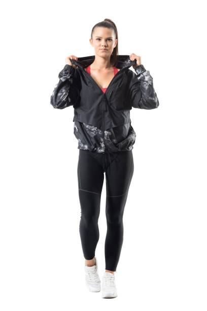 Smiling young active sporty female jogger in warm autumn sportswear. stock photo
