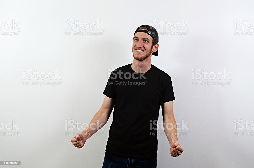 Smiling Young Adult Male in Dark T-Shirt and Baseball Hat stock photo