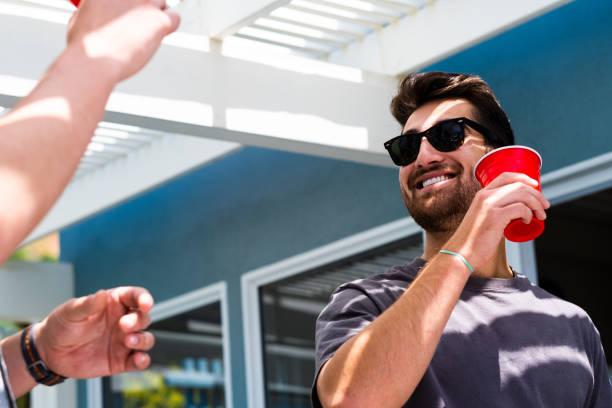 lächelnde junge adultsmänner in sonnenbrille mit rotcup - lustige trinkspiele stock-fotos und bilder