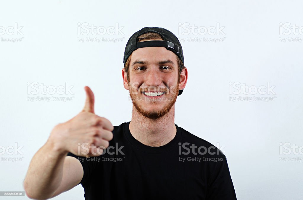 Smiling Young Adult Male Shows His Thumbs Up stock photo