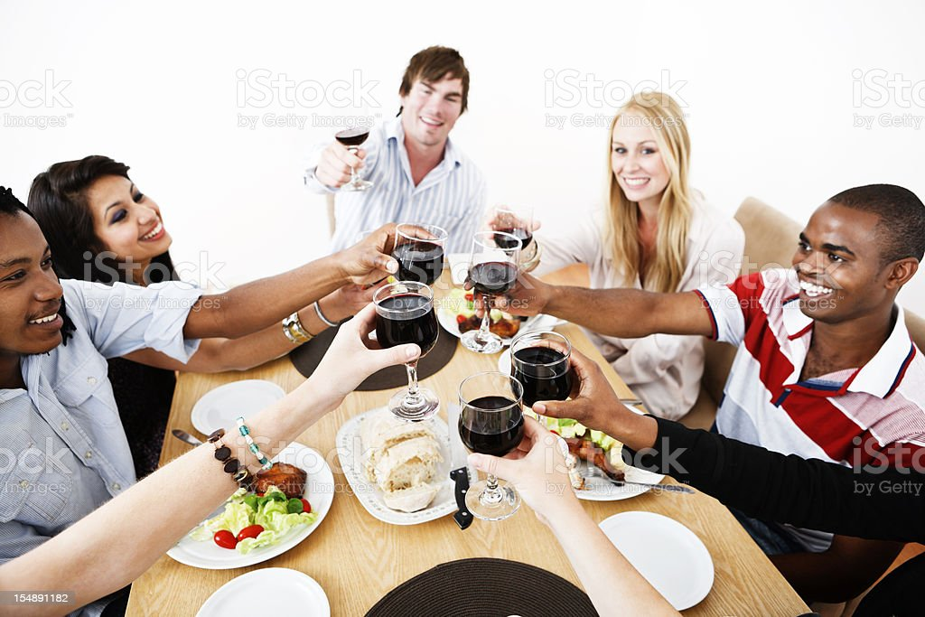 Smiling young adults toast in red wine at dinner table royalty-free stock photo