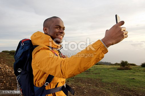 Portrait of smiling young african american male hiker taking selfie outdoors