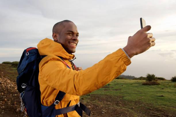 lächelnd junge afrikanische amerikanische männliche Wanderer machen selfie im Freien – Foto