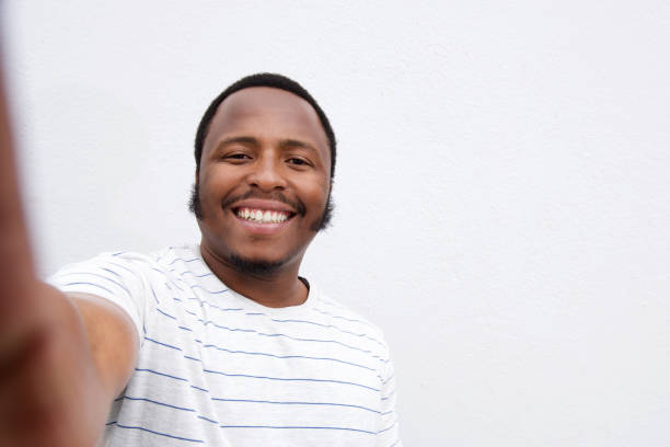 smiling young african american man taking selfie Portrait of smiling young african american man taking selfie against isolated white background afro caribbean ethnicity stock pictures, royalty-free photos & images