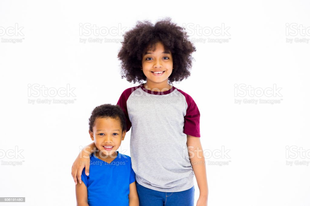 Smiling young African American sister and brother isolated over white background stock photo
