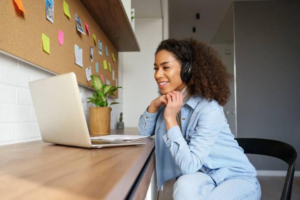 het glimlachende jonge afrikaanse amerikaanse tienermeisje draagt hoofdtelefoonsvideo die op laptop roept. gelukkige gemengde ras mooie vrouwenstudent die computerscherm bekijkt die webinar bekijkt of videopraatje door webcam doet. - e learning stockfoto's en -beelden