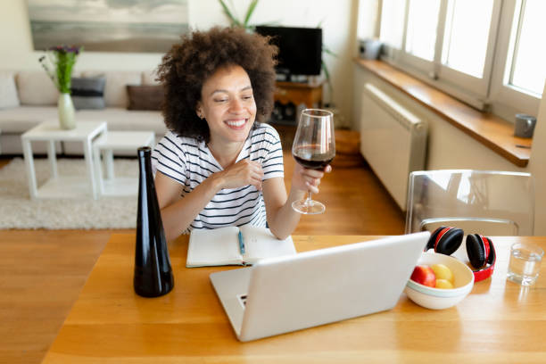 Smiling young African American woman drinking red wine stock photo