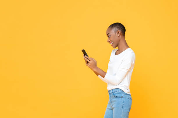 Smiling young African American woman using smartphone  isolated on yellow studio background stock photo