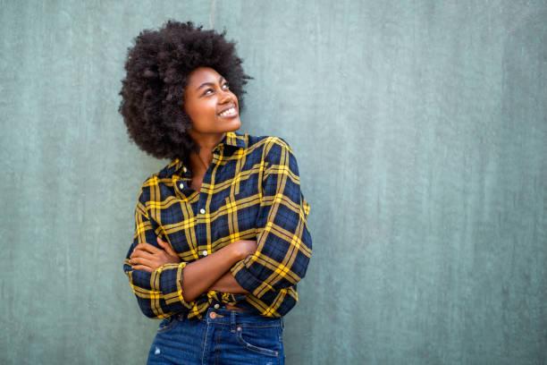 lächelnde junge afrikanische amerikanische Frau mit Afro-Haar stehenarme Arme gekreuzt und nach oben schauen – Foto