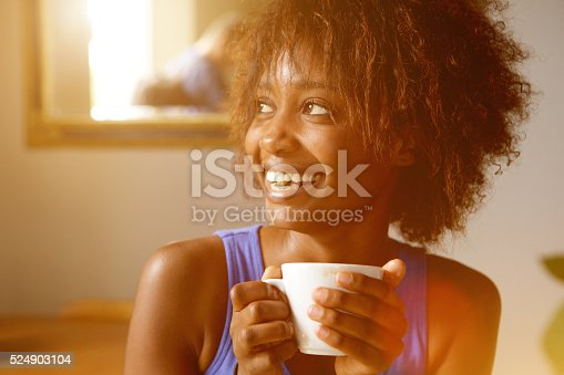 Close up portrait of a smiling young african american woman with coffee cup