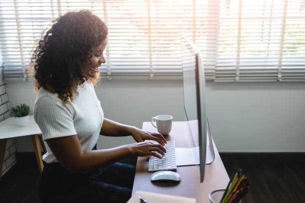 Smiling young African American Woman working on Computer. stock photo