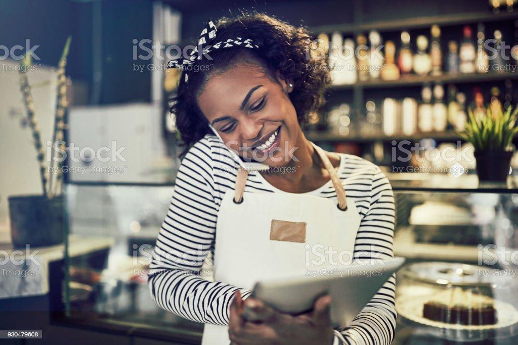 Sonriente joven empresario africano ocupado trabajando en su café - foto de stock
