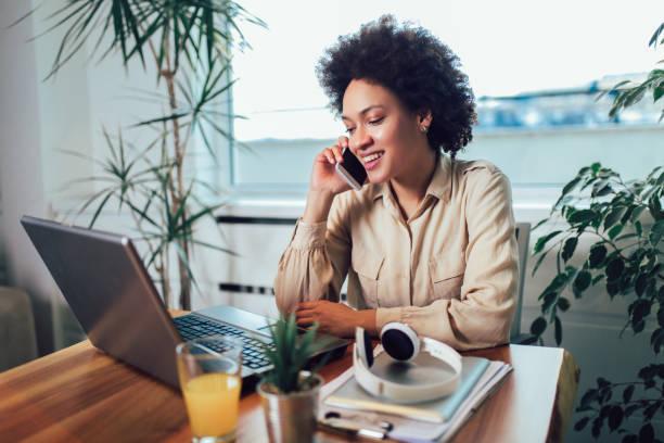 Sonriente a joven empresaria africana sentada en un escritorio en su oficina trabajando en línea con un ordenador portátil - foto de stock