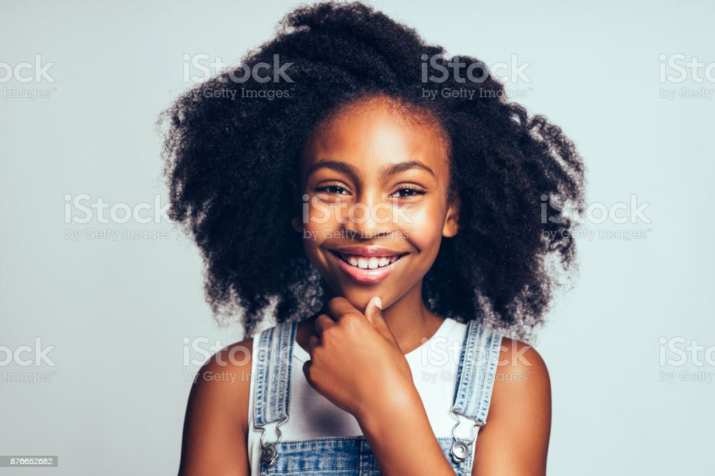Smiling young African girl standing happily against a gray background Cute young African girl with long curly hair smiling and wearing dungarees standing with her hand on her chin against a gray background Adolescence Stock Photo