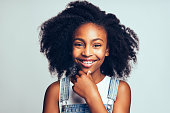 Cute young African girl with long curly hair smiling and wearing dungarees standing with her hand on her chin against a gray background