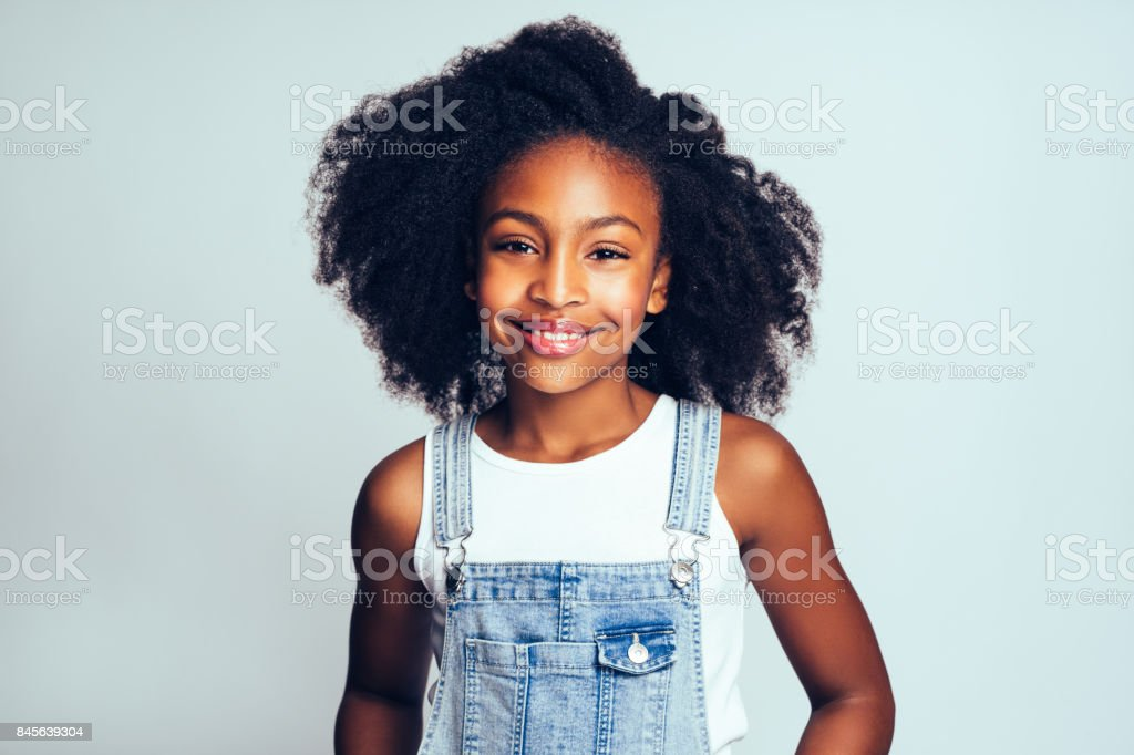Smiling young African girl wearing dungarees against a gray background stock photo