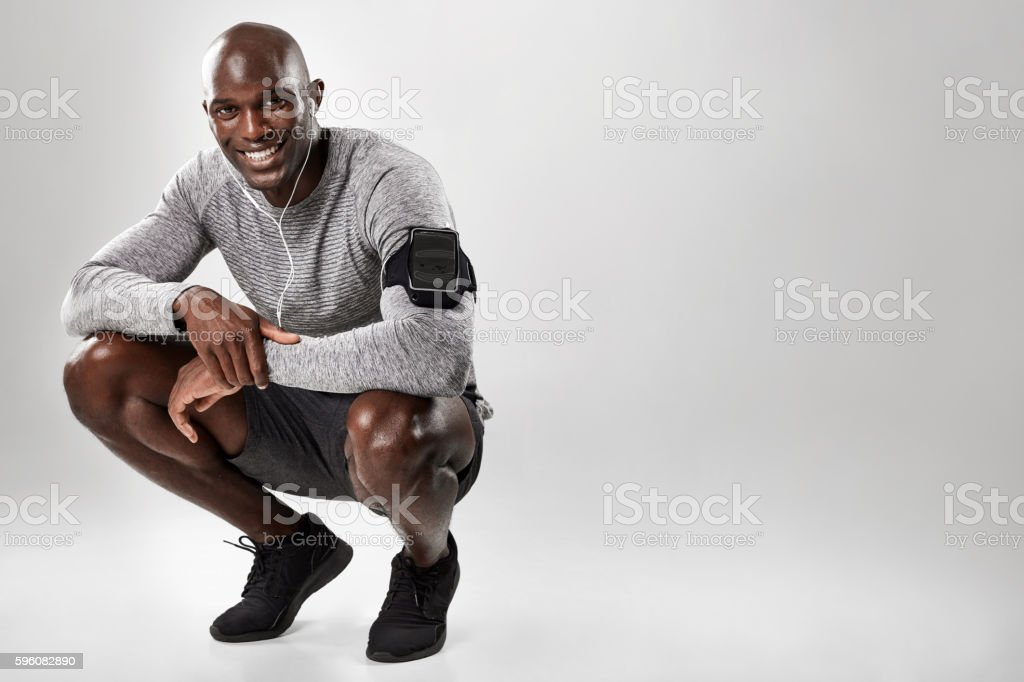 Smiling young african man on grey background stock photo