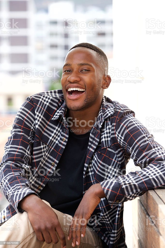 Smiling young african man sitting on a bench outdoors stock photo