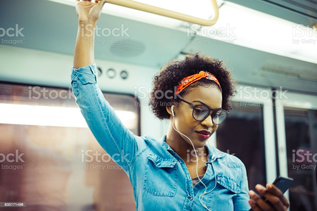 Smiling young African woman listening to music on the subway stock photo