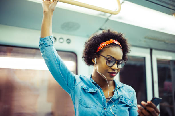 Smiling young African woman listening to music on the subway Smiling young African woman listening to music on her cellphone while standing on a subway train during her daily commute subway stock pictures, royalty-free photos & images