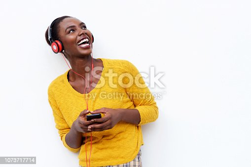 Portrait of smiling young african woman listening to music with headphones and mobile phone against isolated white background