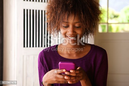 Close up portrait of a smiling young african woman looking at cell phone
