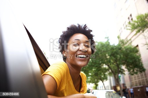 508455188 istock photo Smiling young african woman looking out the car window 508459466