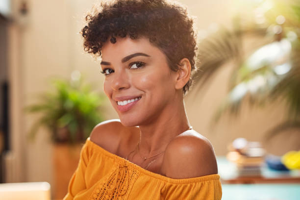 Smiling young african woman Portrait of natural beautiful girl smiling and looking at camera. Closeup face of brazilian young woman with curly hair. Charming african woman sitting at cafeteria. short hair stock pictures, royalty-free photos & images