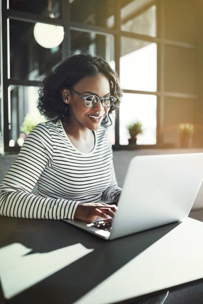 微笑年輕的非洲婦女坐在桌子上工作線上 - 垂直構圖 個照片及圖片檔
