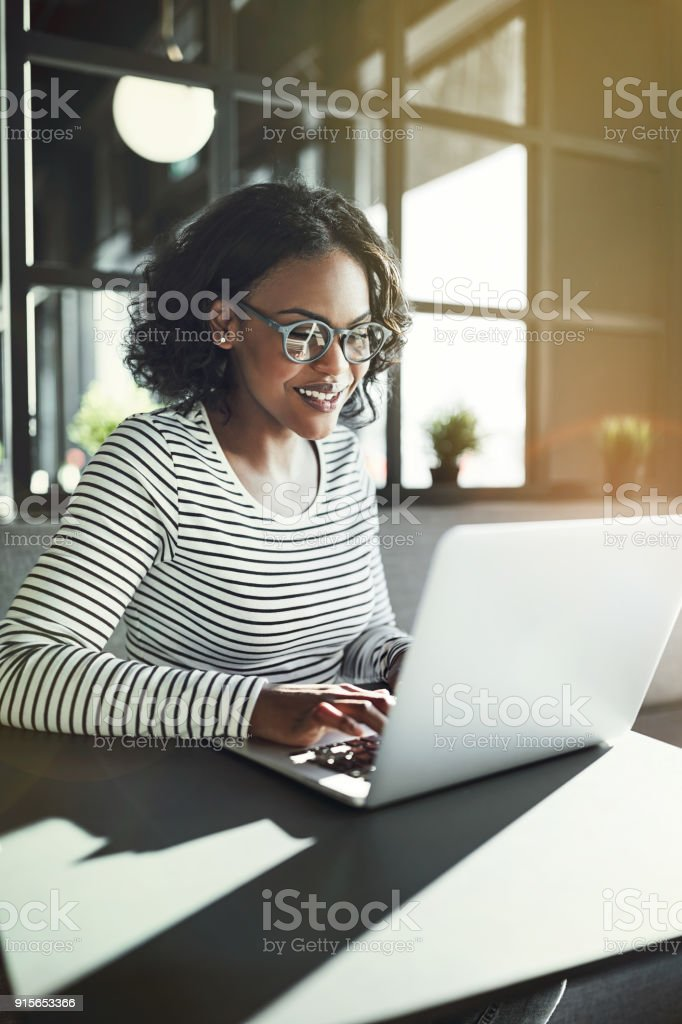 Smiling young African woman sitting at a table working online stock photo