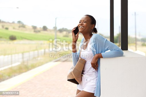 862201618 istock photo Smiling young african woman standing with cell phone and bag 528300114
