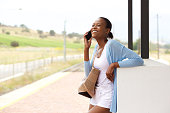 istock Smiling young african woman standing with cell phone and bag 528300114
