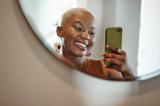 Smiling young African woman with short blond hair taking a selfie with her smart phone in front of a mirror at home