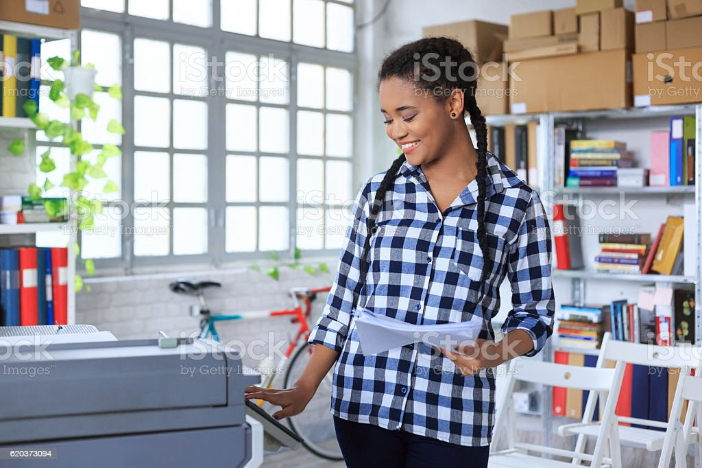 Smiling young african woman using copy machine in modern office stock photo
