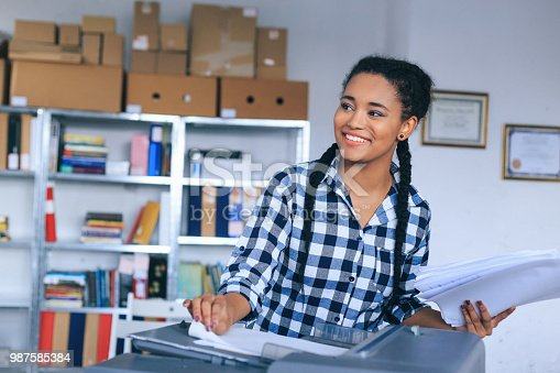 istock Smiling young african woman using copy machine in modern office 987585384